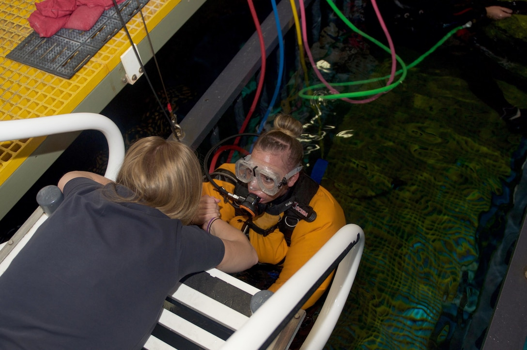 Instructor helping soldier out of shark tank.