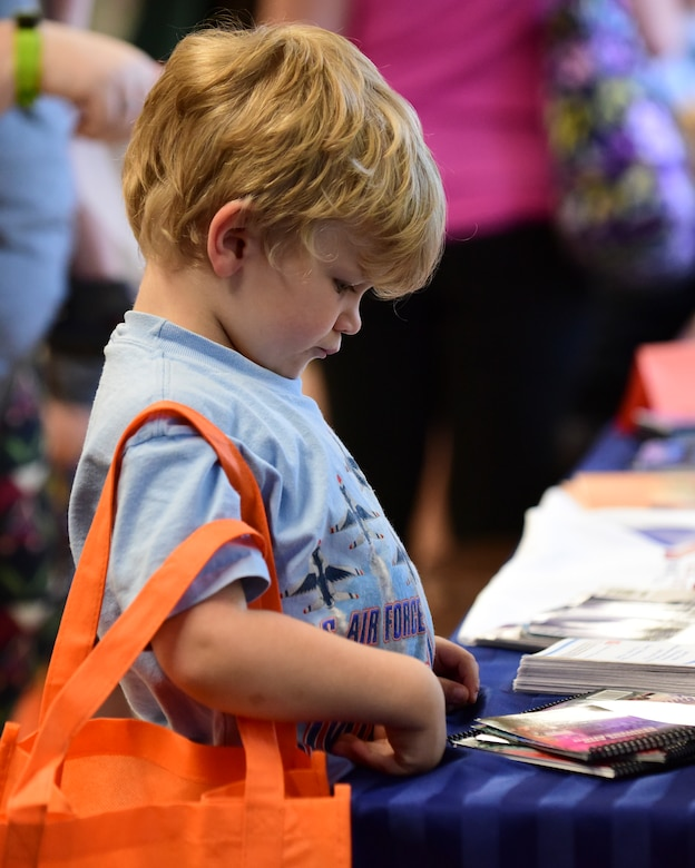 A young member of Team Whiteman looks at an Airman & Family Readiness Center informational booklet during the Back-to-School Brigade event at Whiteman Air Force Base, Mo., Aug. 8, 2017. Students were given tote bag to fill with school supplies and resources to help them start the new school year off right. (U.S. Air Force photo by Staff Sgt. Danielle Quilla)