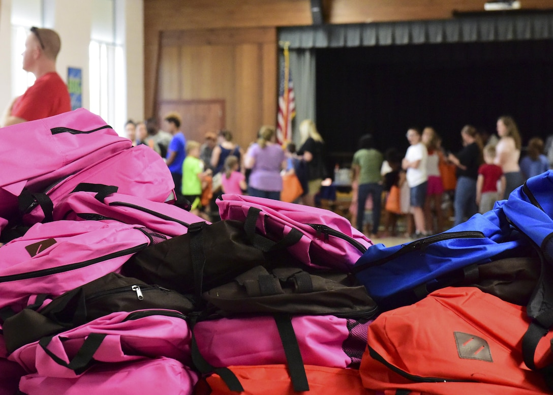 A stack of backpacks wait to be chosen by students during the Back-to-School Brigade event at Whiteman Air Force Base, Mo., Aug. 8, 2017. A total of 300 backpacks and $2,700 worth of supplies were donated to help students start the new school year right. (U.S. Air Force photo by Staff Sgt. Danielle Quilla)