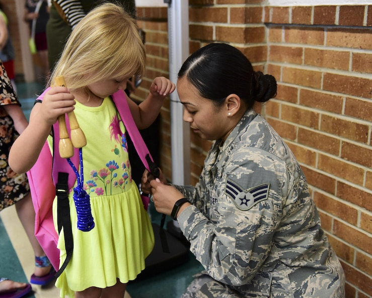 U.S. Air Force Senior Airman Tiffani-Amber Petit, a physical therapy technician with the 509th Medical Operations Squadron, right, helps adjust the backpack straps for Delilah Gordon, a pre-kindergarten student who is the daughter of Staff Sgt. Samuel Gordon, during the Back-to-School Brigade event at Whiteman Air Force Base, Mo., Aug. 8, 2017. Petit made sure the backpack fit comfortably and did not weigh more than 10 percent of the student's bodyweight. (U.S. Air Force photo by Staff Sgt. Danielle Quilla)