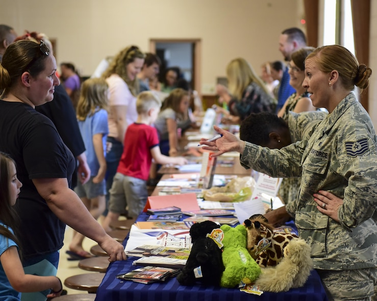 U.S. Air Force Tech. Sgt. Kira Otero, a readiness NCO with the Airman & Family Readiness Center (A&FRC), speaks to a family about the programs the center offers during the Back-to-School Brigade event at Whiteman Air Force Base, Mo., Aug. 8, 2017. In addition to the A&FRC, programs such as Child Care Aware and Exceptional Family Member Program were present to help ensure families had all the resources they needed to make it a successful school year. (U.S. Air Force photo by Staff Sgt. Danielle Quilla)
