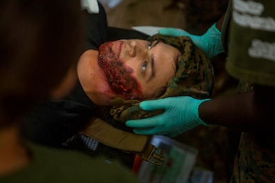 """A patient receives casualty care from the corpsmen of Medical Battalion, 1st Marine Logistics Group, during a patient scenario as part of training exercise Pico De Gallo at Camp Pendleton, Calif., Aug. 15, 2017. The surgeon tent allows Sailors of 1st Med Bn to quickly stabilize patients before sending them off to a higher echelon of care. Training exercise Pico De Gallo provides Marines and Sailors with the knowledge to execute hyper-realistic, quick casualty training to further refine """"the finest surgical company in the Marine Corps"""". (U.S. Marine Corps photo by Lance Cpl. Joseph Sorci)"""