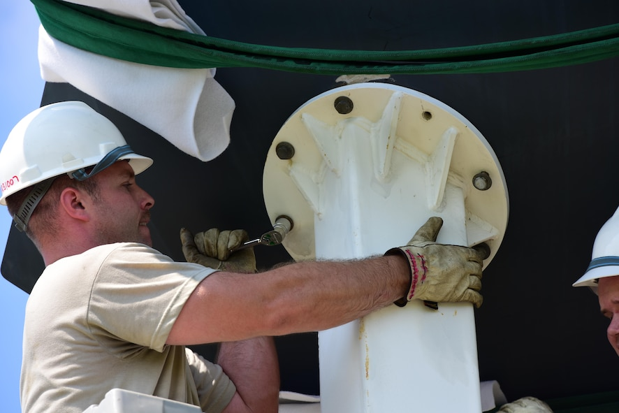 U.S. Air Force Tech. Sgt. William Conant, a 131st Maintenance Group maintenance flight phase technician, tightens down a bolt to hold the B-2 Spirit replica into place at Whiteman Air Force Base, Mo., Aug. 10, 2017. The aerospace repair and phase inspection shops led the project of replacing the static after the old display was removed for repairs.