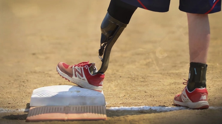 A person with a black prosthetic metal leg in a red athletic shoe puts his foot on a base.