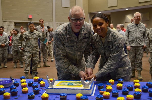 Airman Celeste Perry, 68th Network Warfare Squadron and youngest 24th Air Force Airman in San Antonio, joins Maj. General Chris Weggeman, 24th AF Commander, in cutting the cake to celebrate the NAF's eighth birthday Aug 18, 2017, at Joint Base San Antonio-Lackland, Texas.
