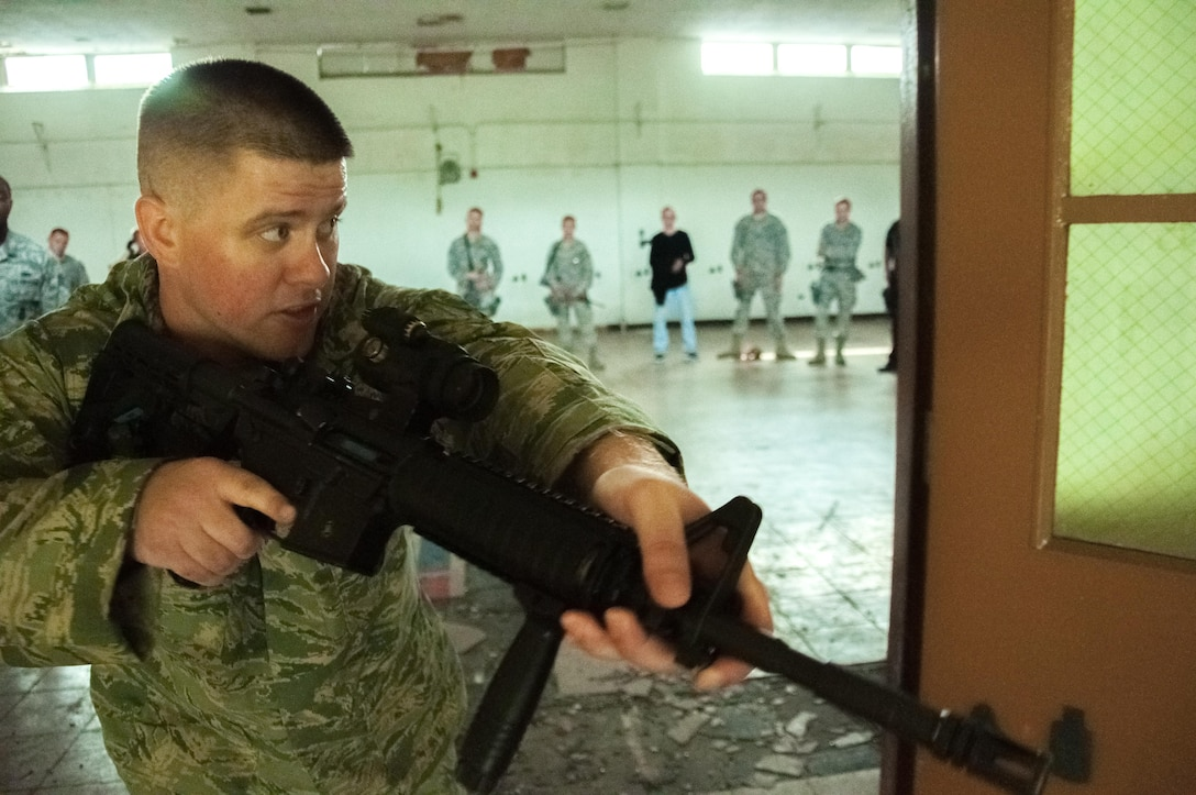 DAYTON, Ohio – Staff Sgt. Malcolm MacDougall, 88th Security Forces Squadron unit instructor, demonstrates the correct way to enter a room during clearing operations to 88 SFS defenders during annual training July 12. MacDougall instructs the week-long course two to three times a month to classes that average 12 to 15 students. (U.S. Air Force photo/John Harrington)