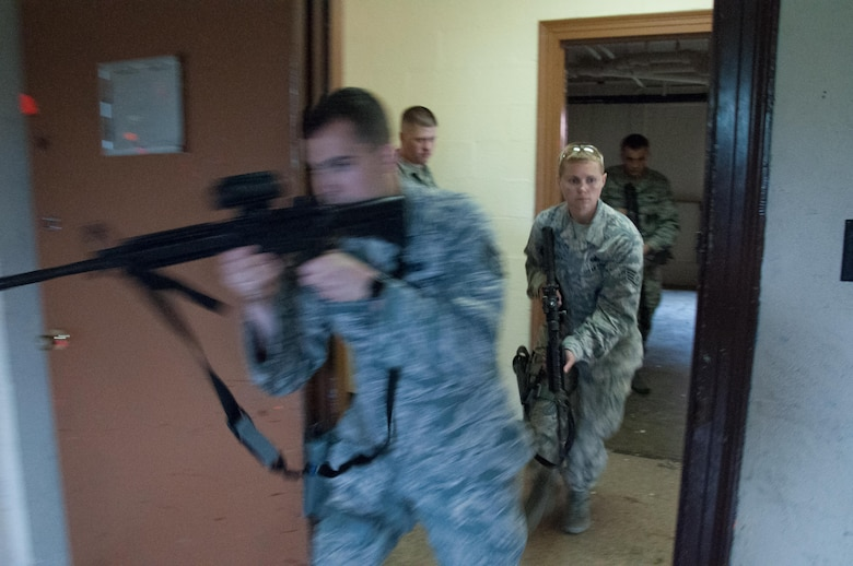 DAYTON, Ohio – Staff Sgt. Kyle Brophy (left), 88th Security Forces Squadron investigator, enters a room first during a walkthrough prior to conducting clearing exercises with Staff Sgt. Heather Albright, 88 SFS canine handler, entering behind him during annual training July 12. Defenders from throughout 88 SFS learn to work together in executing security missions in the week-long course. (U.S. Air Force photo/John Harrington)