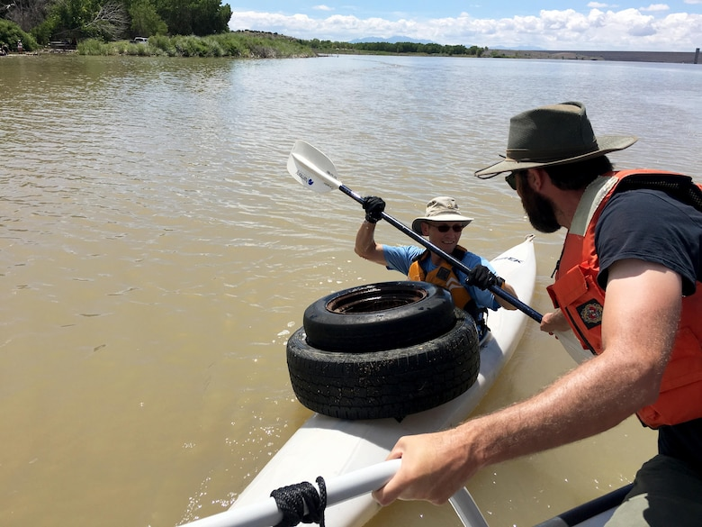 "COCHITI LAKE, N.M. – A volunteer drops off two tires during the ""Cochiti Sweep"" event, Aug. 12, 2017."