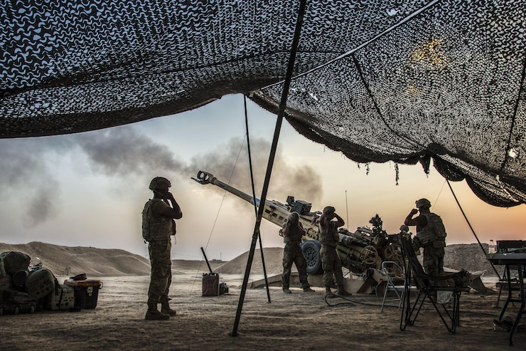 Soldiers standing near overhead netting cover their ears as a howitzer is fired.
