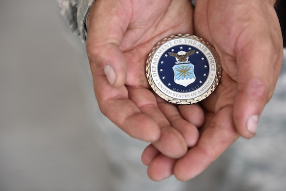 Staff Sgt. Kyle Yoder of the 380th Expeditionary Aircraft Maintenance Squadron holds out a coin awarded to him by Secretary of the Air Force Heather Wilson at Al Dhafra Air Base, United Arab Emirates, Aug. 18, 2017.