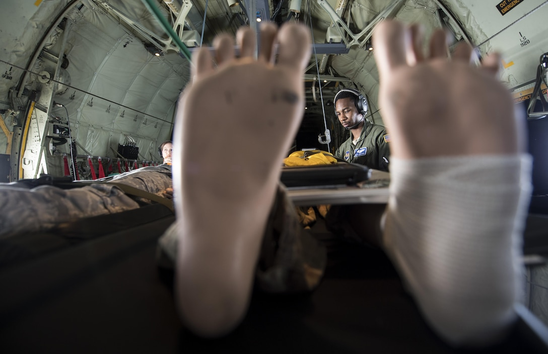 U.S. Air Force Staff Sgt. Tedario Cassel, 86th Aeromedical Evacuation Squadron aeromedical evacuation technician, examines a medial dummy during a training mission while flying to Ramstein Air Base, Germany, Aug. 17, 2017. Four medical dummies were used during the aeromedical training mission for the 86th AES Airmen to practice procedures to maintain readiness. (U.S. Air Force photo by Senior Airman Tryphena Mayhugh)