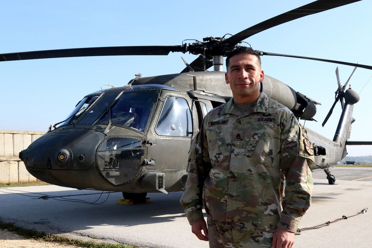 Staff Sgt. Oscar Morales stands in front of a helicopter.