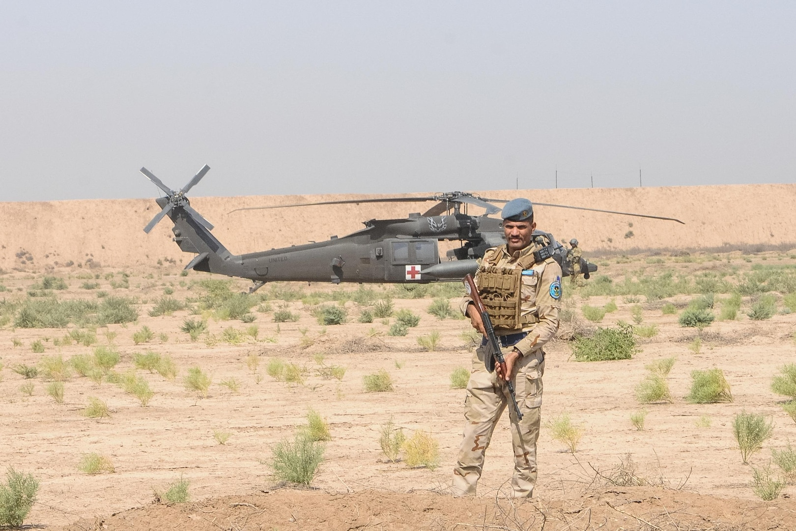 A member of the Iraqi Security Forces establishes a security perimeter around an HH-60M Black Hawk helicopter from the 2-149th General Support Aviation Battalion, Task Force Rough Riders, during the aerial response force exercise at Camp Taji Military Complex, Iraq, August 13,2017. The ISF provided security to an HH-60M Black Hawk helicopter that had been grounded due to simulated maintenance issues. This training is part of the overall Combined Joint Task Force – Operation Inherent Resolve building partner capacity mission which focuses on training and improving the capability of partnered forces fighting ISIS. CJTF-OIR is the global Coalition to defeat ISIS in Iraq and Syria. (US Army Photo by Capt. Stephen James)