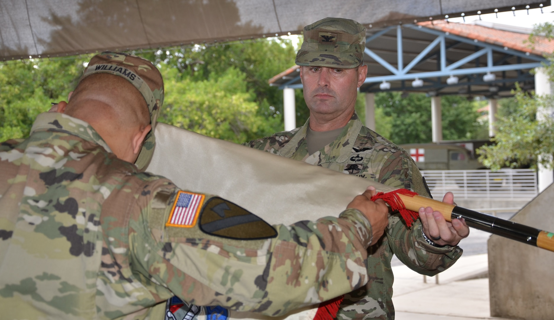 Col. Jeffrey Burris (right) and Command Sgt. Maj. Charles Williams (left) unfurl the colors during the 410th Contracting Support Brigade's uncasing ceremony Aug. 15 at the U.S. Army Medical Department Museum, Joint Base San Antonio-Fort Sam Houston, Texas. Burris is the 410th CSB commander, and Williams is the 410th CSB sergeant major.