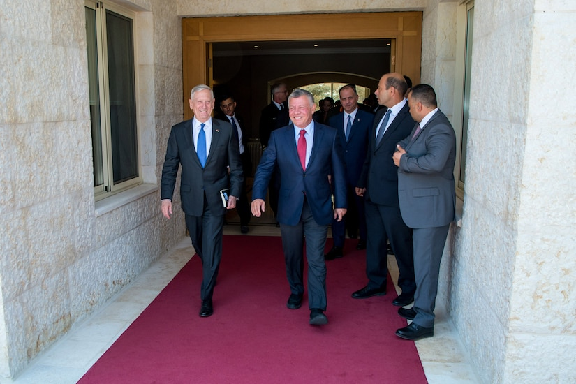 Defense Secretary Jim Mattis walks with King Abdullah II of Jordan on a red carpet.