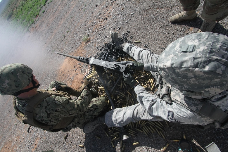 Gunner Staff Sgt. Joshua Hopkins fires the M2 .50 caliber machine gun while assistant gunner U.S. Petty Officer 3rd Class Derek Dick monitors ammunition during heavy weapons firing on Fort Bliss' Range 39.
