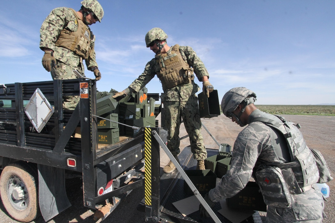 From left, U.S. Navy Petty Officers 2nd Class Zachary Shoemaker and Christopher Norberto, and U.S. Air Force Senior Airman Timothy Montano load up empty ammunition cans after heavy weapons firing at Fort Bliss, Texas, July 26, 2017.