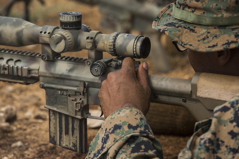 """Hospitalman Third Class Cory Jackson, a corpsman with Weapons Company, 2nd Battalion, 3rd Marine Regiment checks the charging handle of an M110 Semi-Automatic Sniper System during a pre-scout sniper course at Pu'uloa Range Training Facility aboard Marine Corps Base Hawaii, August 14, 2017. The known distance qualification course involves firing at moving targets from the 300, 500, and 600 yard lines; engaging """"stop and go"""" and """"bobber"""" targets at the 700 and 800; shooting from the maximum range of 1,000 yards, and is designed to enhance the Marines' capabilities to engage targets at known distances and alternate positions. (U.S. Marine Corps photo by Lance Cpl. Isabelo Tabanguil)"""