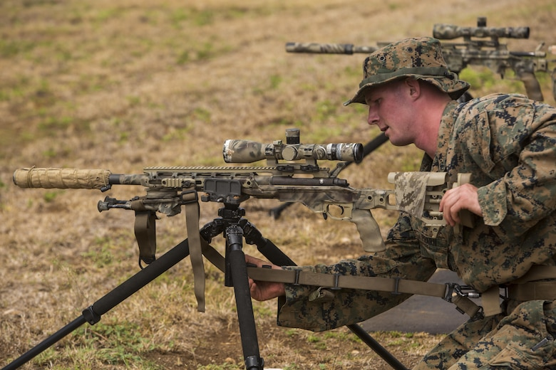 """Lance Cpl. William Pearn, a scout sniper candidate with Weapons Company, 2nd Battalion, 3rd Marine Regiment, secures a strap to an M40A6 sniper rifle during a pre-scout sniper course at Pu'uloa Range Training Facility aboard Marine Corps Base Hawaii, August 14, 2017. The known distance qualification course involves firing at moving targets from the 300, 500, and 600 yard lines; engaging """"stop and go"""" and """"bobber"""" targets at the 700 and 800; shooting from the maximum range of 1,000 yards, and is designed to enhance the Marines' capabilities to engage targets at known distances and alternate positions. (U.S. Marine Corps photo by Lance Cpl. Isabelo Tabanguil)"""