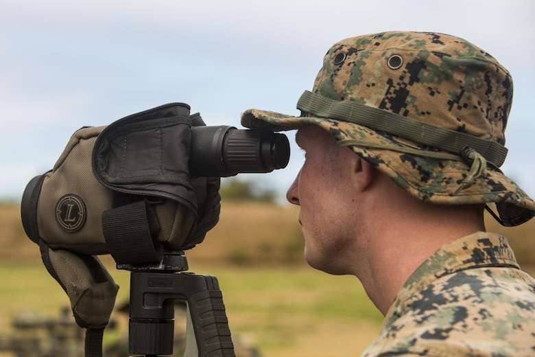Lance Cpl. William Pearn, a scout sniper candidate with Weapons Company, 2nd Battalion, 3rd Marine Regiment, sights down range as a spotter during a pre-scout sniper course at Pu'uloa Range Training Facility aboard Marine Corps Base Hawaii, August 14, 2017. Spotters help the sniper account for wind, elevation, atmospherics and observe the placement of the last shot the shooter fired. The known distance qualification course is designed to enhance the Marines' capabilities to engage targets at known distances and alternate positions. (U.S. Marine Corps photo by Lance Cpl. Isabelo Tabanguil)