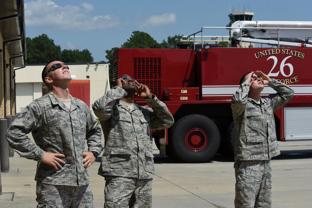 """Members of team Seymour observe the """"Great American Solar Eclipse"""" using eclipse glasses, Aug. 21, 2017, at Seymour Johnson Air Force Base, North Carolina. Eclipse viewers on base observed 94% maximum obstruction. (U.S. Air Force photo by Airman 1st Class Victoria Boyton)"""
