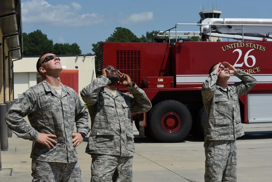 "Members of team Seymour observe the ""Great American Solar Eclipse"" using eclipse glasses, Aug. 21, 2017, at Seymour Johnson Air Force Base, North Carolina. Eclipse viewers on base observed 94% maximum obstruction. (U.S. Air Force photo by Airman 1st Class Victoria Boyton)"