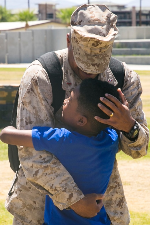 Chief Warrant Officer 3 Marcus Gilmore, personnel officer, 7th Marine Regiment, hugs his son, Zarion Gilmore, at Victory Park aboard the Marine Corps Air Ground Combat Center, August 18, 2017. 7th Marines completed a nine month deployment as the command element of Special Purpose Marine Air-Ground Task Force – Crisis Response – Central Command 17.1. (U.S. 