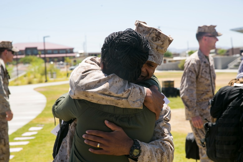 Chief Warrant Officer 3 Marcus Gilmore, personnel officer, 7th Marine Regiment, hugs his wife at Victory Park aboard the Marine Corps Air Ground Combat Center, August 18, 2017. 7th Marines completed a nine month deployment as the command element of Special Purpose Marine Air-Ground Task Force – Crisis Response – Central Command 17.1. (U.S. Marine Corps photo by Lance Cpl. Isaac Cantrell)