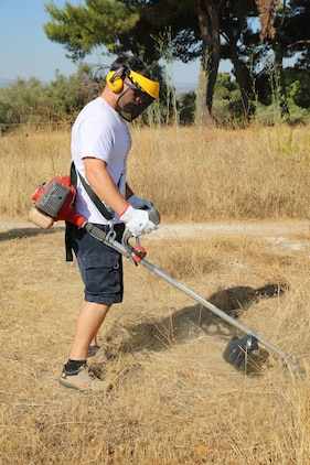A Marine with Special Purpose Marine Air-Ground Task Force-Crisis Response-Africa logistics combat element cuts grass using a weed-whacker during a clean-up event at the Eurialo Castle in Siracusa, Italy, Aug 3, 2017. Marines and Sailors with SPMAGTF-CR-AF LCE joined Italian volunteers in restoring the 2,400 year-old ancient piece of history. (U.S. Marine Corps photo by Lance Cpl. Patrick Osino)
