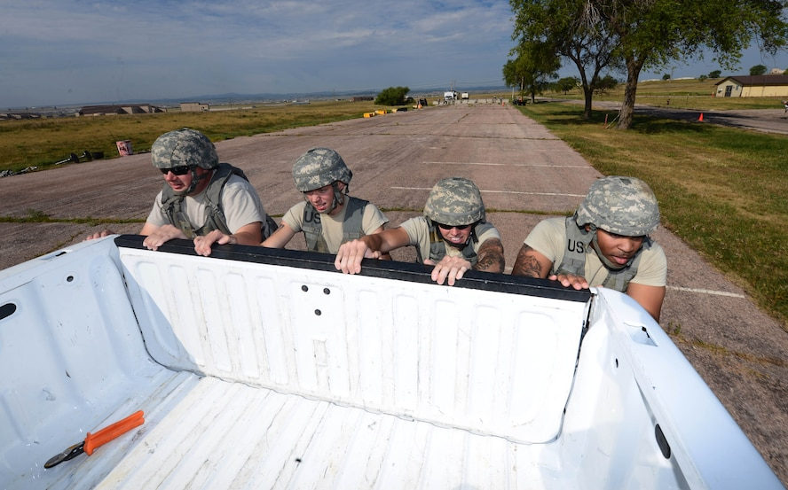 Airmen assigned to the 28th Civil Engineer Squadron push a six-passenger vehicle during the Prime Base Engineer Emergency Force (BEEF) challenge at Ellsworth Air Force Base, S.D., Aug. 17, 2017.
