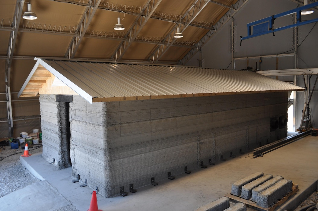 A barracks hut constructed with the Automated Construction of Expeditionary Structures is a new construction technology that prints concrete structures. The printer reduces building materials shipped by half and construction manpower requirements by 62 percent when compared to expedient plywood construction in overseas military construction. This hut resides at the Construction Engineering Research Laboratory in Champaign, Illinois.