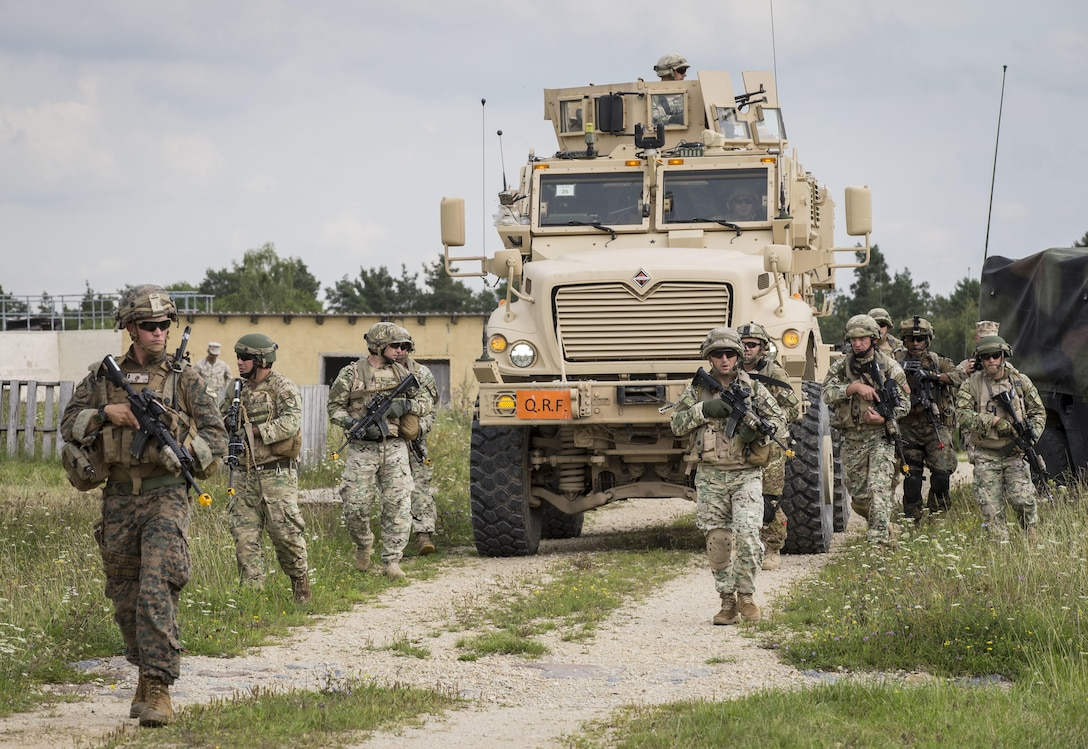 HOHENFELS, Germany – U.S. Marine 1st Lt. Matt Miller (left), a Charlie Company infantry advisor with the Georgia Deployment Program-Resolute Support Mission Georgia Liaison Team, and soldiers with the 31st Georgian Light Infantry Battalion, conduct a patrol while in route to a key leader engagement during the Georgia Deployment Program Mission Rehearsal Exercise aboard the Joint Multinational Readiness Center, Hohenfels, Germany, Aug. 17, 2017. The MRE is the culminating event of the GDP-RSM where GLT and Marines from 6th Air Naval Gunfire Liaison Company, Force Headquarters Group, Marine Forces Reserve, work alongside the 31st Georgian Light Infantry Battalion to prepare and demonstrate that they are ready to deploy to Afghanistan in support of Operation Freedom's Sentinel.  (U.S. Marine Corps photo by Cpl. Kimberly Aguirre/Released)