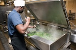 Soldier cooks large quantity of spinach.