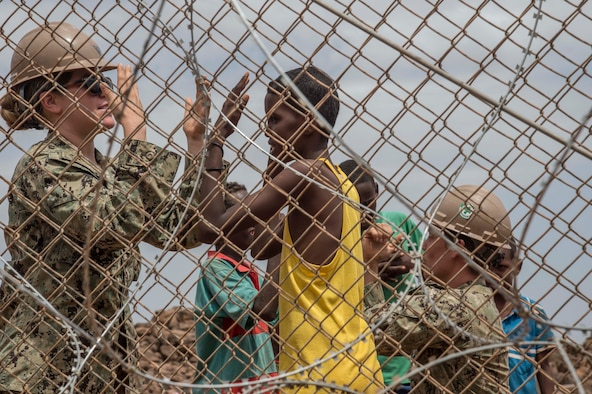 Navy Seabees Petty Officer 3rd Class Lacy P'Pool and Petty Officer 3rd Class Cayla George, assigned to Combined Joint Task Force Horn of Africa, play with local children on a construction site in Djibouti's Arta region, Aug. 17, 2017. The project was started by Naval Mobile Construction Battalion 1, and NMCB 133 will continue working on the project, with plans of completion in 2018. Air National Guard photo by Air Force Tech. Sgt. Joseph Harwood