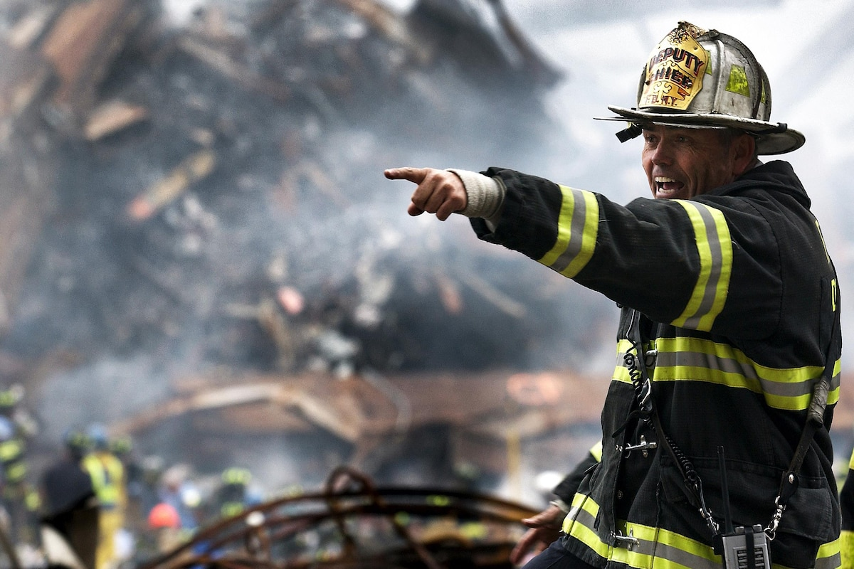 A firefighter instructs rescue teams clearing through debris at ground zero.