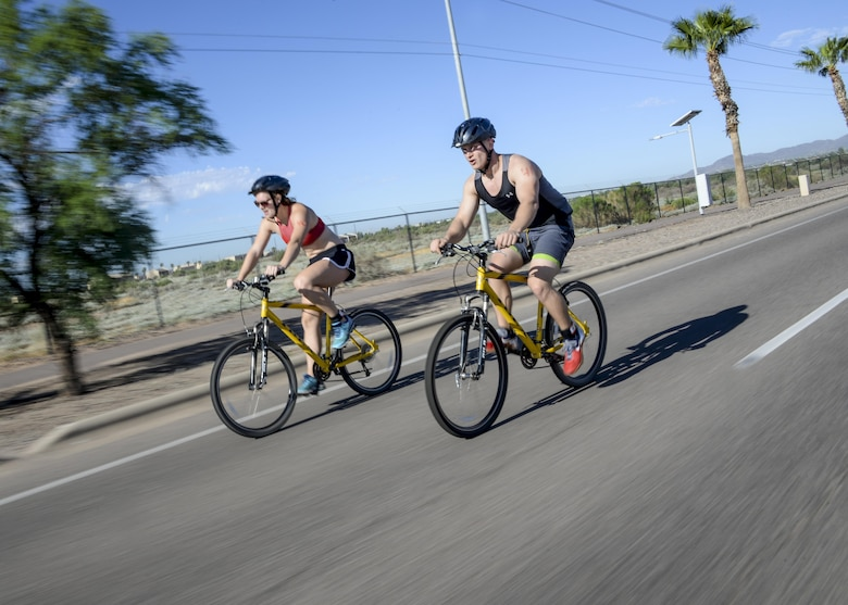 Airmen assigned to the 56th Fighter Wing ride their bikes during the Luke Triathlon held at Luke Air Force Base, Ariz., Aug. 19, 2017. Nearly 70 participants, including active duty, reserve and retirees, participated in the competition. (U.S. Air Force photo/Airman 1st Class Caleb Worpel)