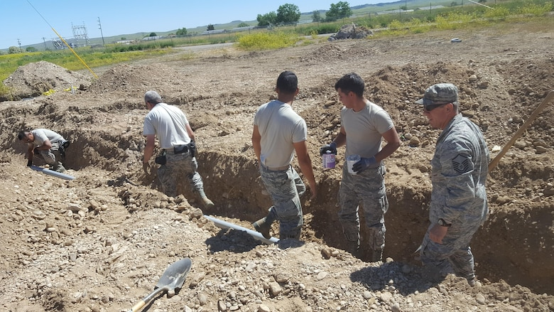 Members of the 106th Rescue Wing Civil Engineering assigned to the New York Air National Guard, dig a ditch for a pipeline at Crow Agency, Montana June 13, 2017. The effort to build and renovate homes for military service veterans of the Native American tribe Crow Nation started in May and will end in September of this year. (U.S. Air Force photo by Airman 1st Class Jonathan De Jesus)