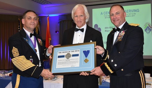 Author and businessman Robert Edsel, center, receives a medal as an honorary member of the Order of the 88th Division from Commanding General of the 88th Regional Support Command Maj. Gen. Patrick Reinert, right, and 88th RSC Command Sgt. Maj. Earl Rocca during an 88th RSC Headquarters and Headquarters Company banquet in Warrens, Wis. on Aug. 19, in honor of the 100 Year Anniversary of the establishment of the 88th Division.