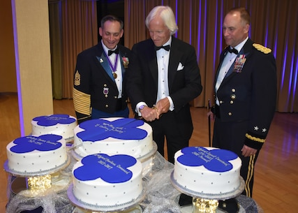Commanding General of the 88th Regional Support Command Maj. Gen. Patrick Reinert, right, and 88th RSC Command Sgt. Maj. Earl Rocca along with author and businessman Robert Edsel, center, conduct a cake cutting ceremony during an 88th RSC Headquarters and Headquarters Company banquet in Warrens, Wis. on Aug. 19, in honor of the 100 Year Anniversary of the establishment of the 88th Division.