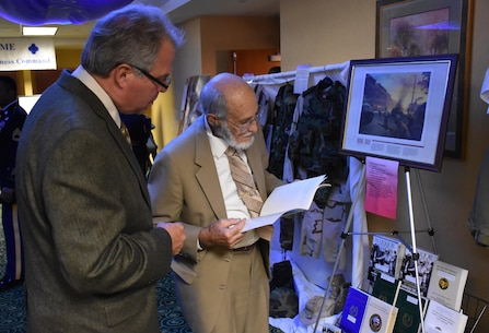 Bruce Abbott, honored guest and 88th Blue Devil Soldier during World War II reads historical publications on display during an 88th Regional Support Command Headquarters and headquarters Company banquet in honor of the 100 Year Anniversary of the establishment of the 88th Division in Warrens, Wis., Aug. 19.