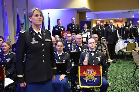 88th Regional Support Command Army Band member CW3 Sharon Toulouse stands at attention after conducting a performance during an 88th RSC Headquarters and Headquarters Company banquet in Warrens, Wis. on Aug. 19, in honor of the 100 Year Anniversary of the establishment of the 88th Division.