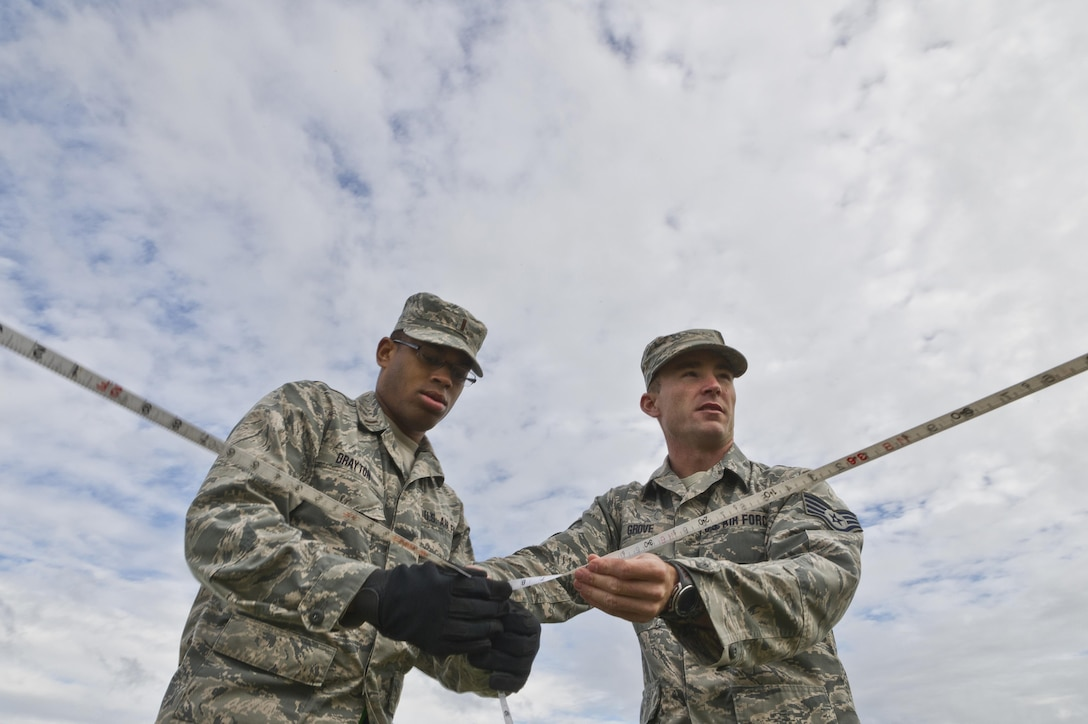 U.S. Air Force 2nd Lt. Justin Drayton, left, 307th Civil Engineer Squadron, Barksdale AFB, La., and Staff Sgt. Brandon Grove, assigned to the 302nd Civil Engineer Squadron, Peterson AFB, Colo., measure out a tent site for a bare base setup at Young Air Assault Strip, Fort McCoy, Wis., Aug. 4, 2017, during exercise Patriot Warrior.