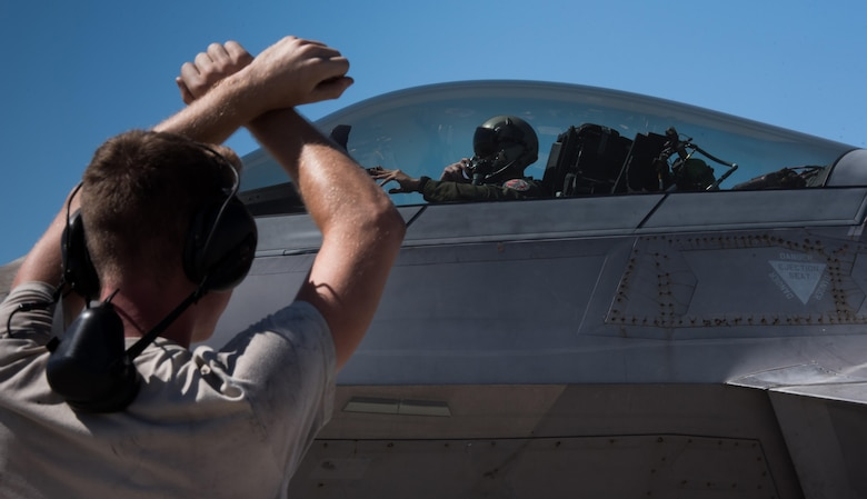 U.S. Air Force Airman 1st Class Joseph Melton, 27th Aircraft Maintenance Unit, marshals in a U.S. Air Force F-22 Raptor from the 94th Fighter Squadron at Nellis Air Force Base, Nev., August 18, 2017. The 94th FS is currently deployed to Red Flag 17-4, taking part in an multi-dimensional simulated air and ground combat environment. (U.S. Air Force photo by Staff Sgt. Carlin Leslie)