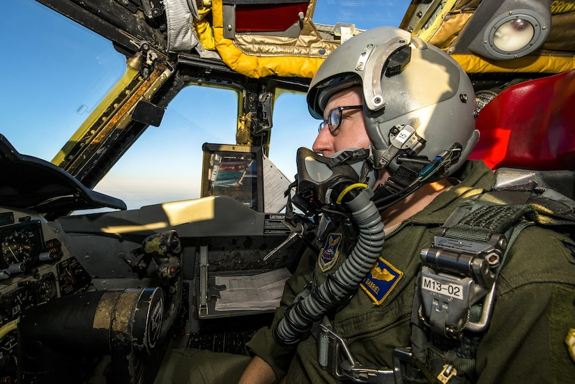 A pilot sits in a cockpit while operating an aircraft.