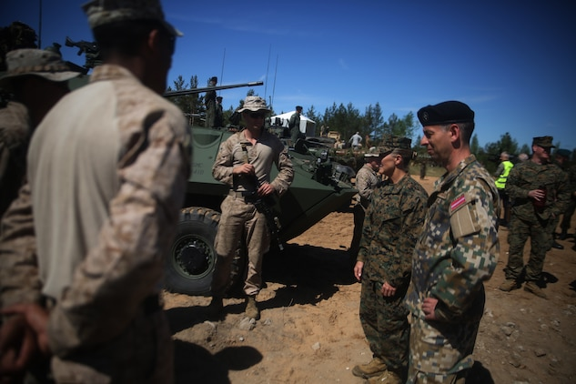 Brig. Gen. Helen G. Pratt, commanding general of 4th Marine Logistics Group, Marine Forces Reserve, and a Latvian soldier speak with U.S. Marines assigned to Marine Corps Forces Europe and Africa during a combined-arms live fire exercise aboard Adazi Military Base, Latvia, June 9, 2017. The event was a part of Exercise Saber Strike 17, a multinational training exercise with NATO Allies and partner nations to increase cohesion and skills through combined-arms training (U.S. Marine Corps photo by Cpl. Sean J. Berry)