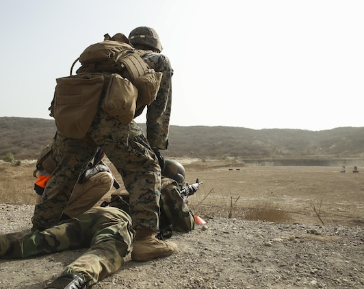 Cpl. Jonah Plemer, a rifleman with Special Purpose Marine Air-Ground Task Force – Crisis Response – Africa, observes the impacts of a soldier with Senegal's 5th Contingent in Mali during an unknown distance range as part of a peacekeeping operations training mission at Thies, Senegal, June 9, 2017. Marines and Sailors with SPMAGTF-CR-AF served as instructors and designed the training to enhance the soldiers' abilities to successfully deploy in support of United Nations peacekeeping missions in the continent. (U.S. Marine Corps photo by Sgt. Samuel Guerra/Released)
