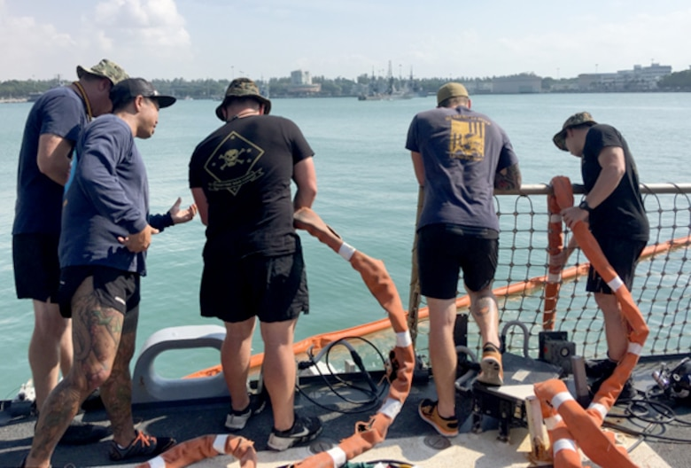 U.S. Navy and Marine Corps divers provide support to the USS John S. McCain (DDG 56) at Changi Naval Base, Singapore Aug. 23, 2017. The McCain sustained significant damage following a collision with the merchant vessel Alnic MC while underway east of the Strait of Malacca and Singapore on Aug. 21, 2017.