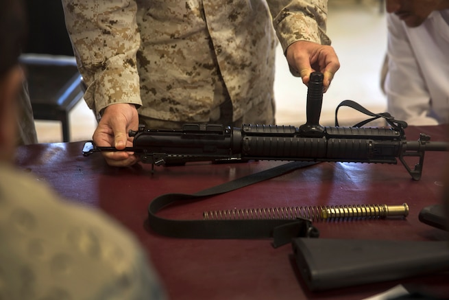A U.S. Marine shows Afghan National police officers how to reassemble the M16A2 assault rifle.