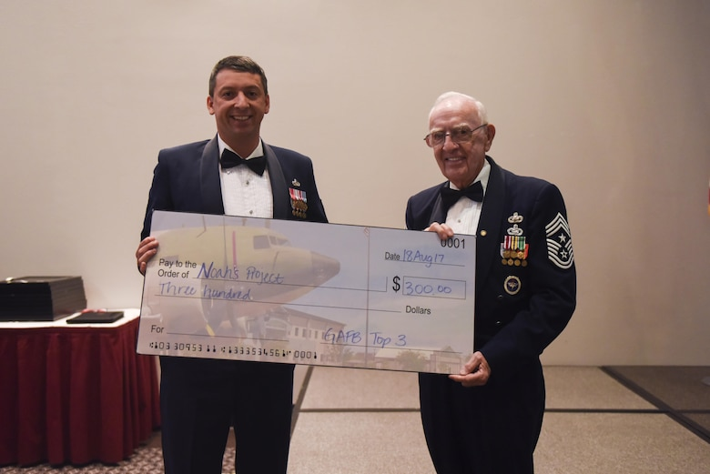 Master Sgt. Douglas Earl, 316th Training Squadron operations superintendent, hands a check to retired Chief Master Sgt. Robert Mehaffey, guest speaker, during the Senior NCO Induction Ceremony at the Event Center on Goodfellow Air Force Base, Texas, Aug. 18, 2017. The check was a donation to Mehaffey's choice of charity. (U.S. Air Force photo by Airman 1st Class Chase Sousa/Released)