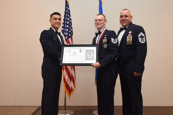 U.S. Air Force Tech. Sgt. Andrew Britt, 316th Training Squadron, receives their certificate of selection from Col. Ricky Mills, 17th Training Wing commander, and Chief Master Sgt. Daniel Stein, 17th Training Group superintendent, during the Senior NCO Induction Ceremony at the Event Center on Goodfellow Air Force Base, Texas, Aug. 18, 2017. (U.S. Air Force photo by Airman 1st Class Chase Sousa/Released)